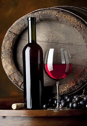 Picture of bottle with glass of wine in front of barrel